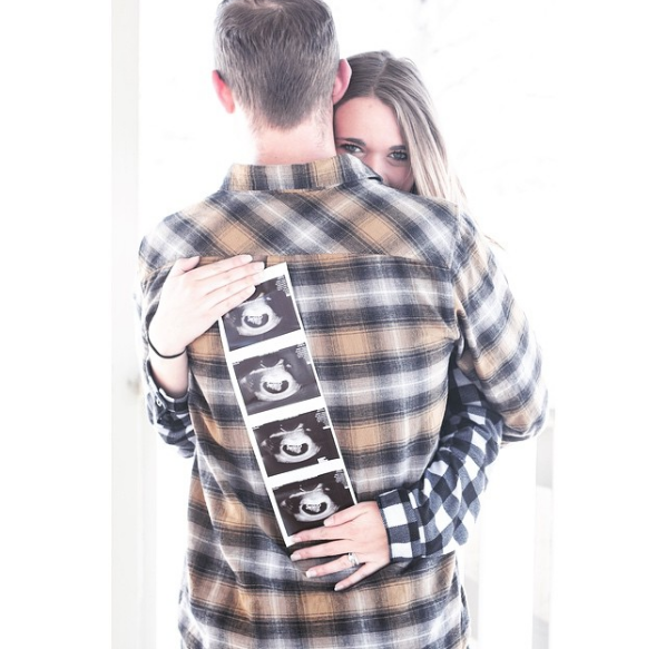 Woman hugs husband and holds up an ultrasound photo strip on his back.