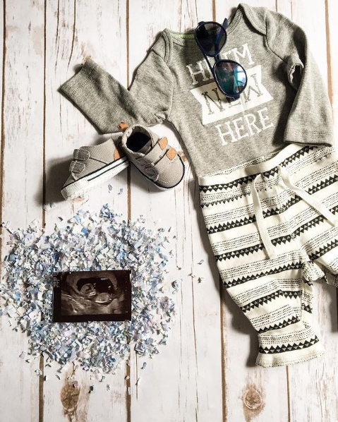 A flat lay with an ultrasound photo and baby clothes.