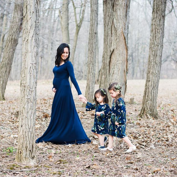 Mom walks through the woods with her two daughters.