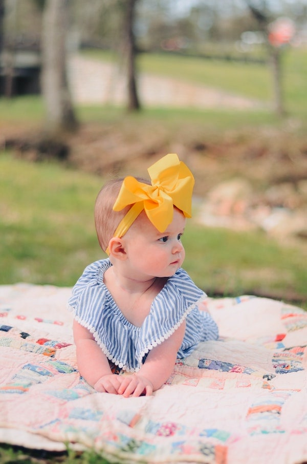 Baby girl with yellow bow lays on blanket.