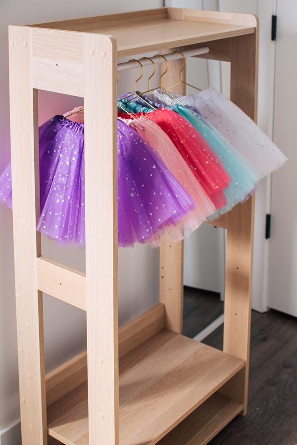 Tutu skirt birthday favors hung on a clothing rack.