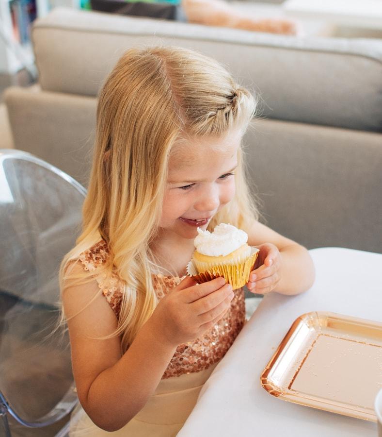 A birthday girl eats a cupcake.