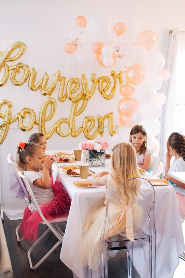 Girls eat lunch at a golden birthday party.