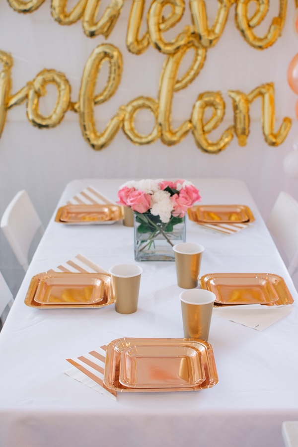 Rose gold place settings on a white table.