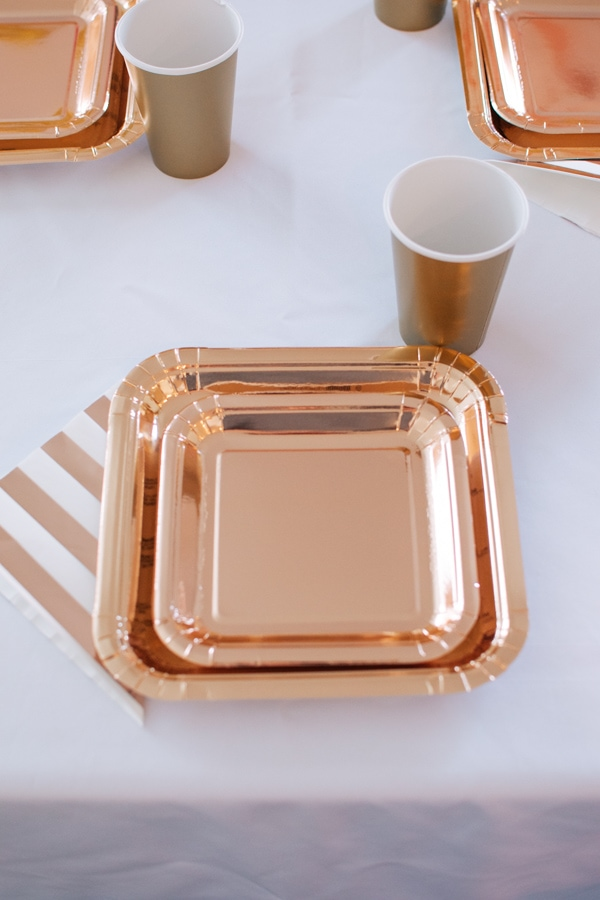 Rose gold birthday tableware on a white table.