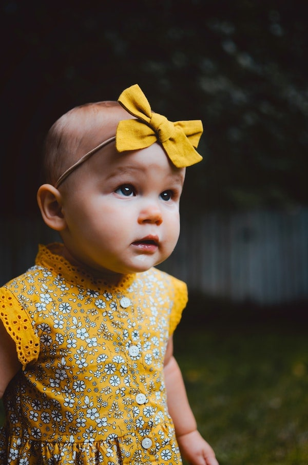 Baby girl wears yellow bow and yellow dress.