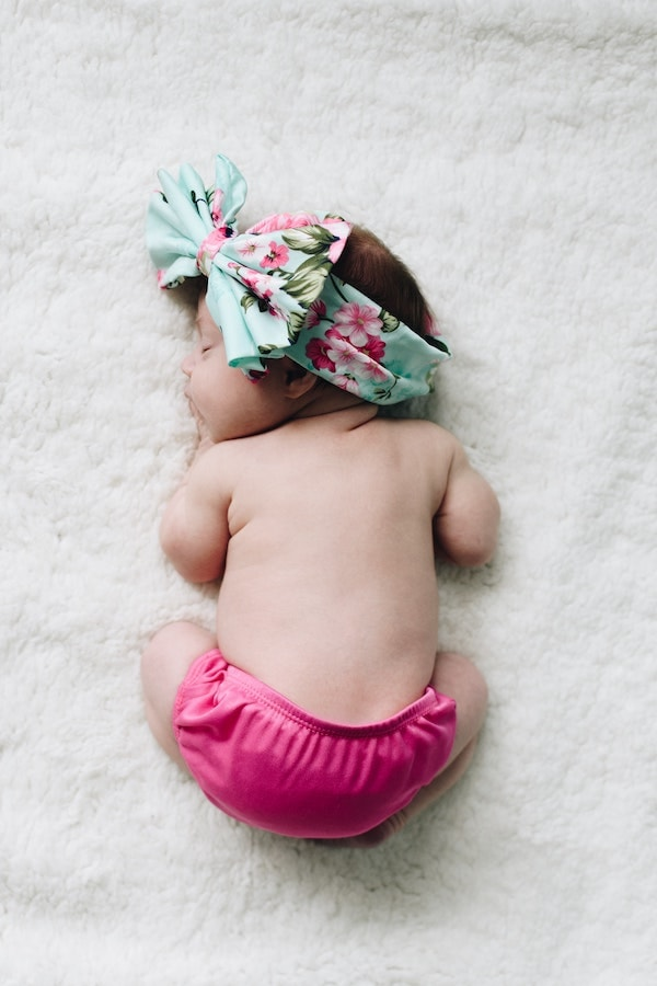 Baby girl with big bow sleeps on her tummy.