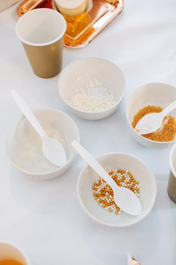 Gold sprinkles in white bowls.