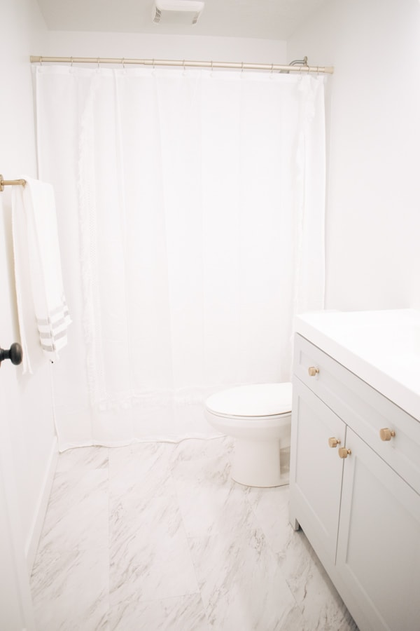 Basement bathroom with white and gray decor.