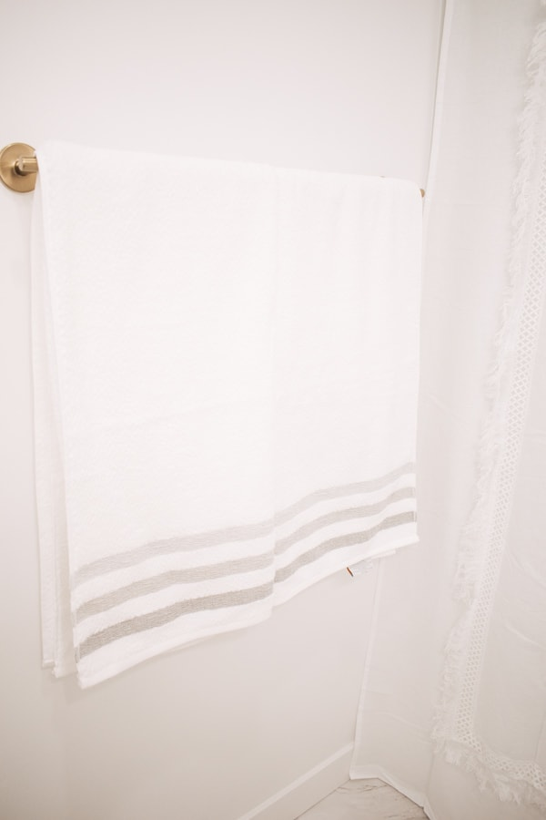 White and gray bath towels on a gold towel bar.