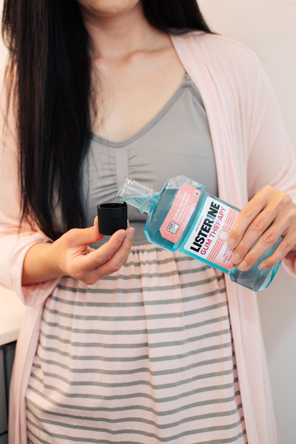 Woman uses Listerine in her healthy daily routine.