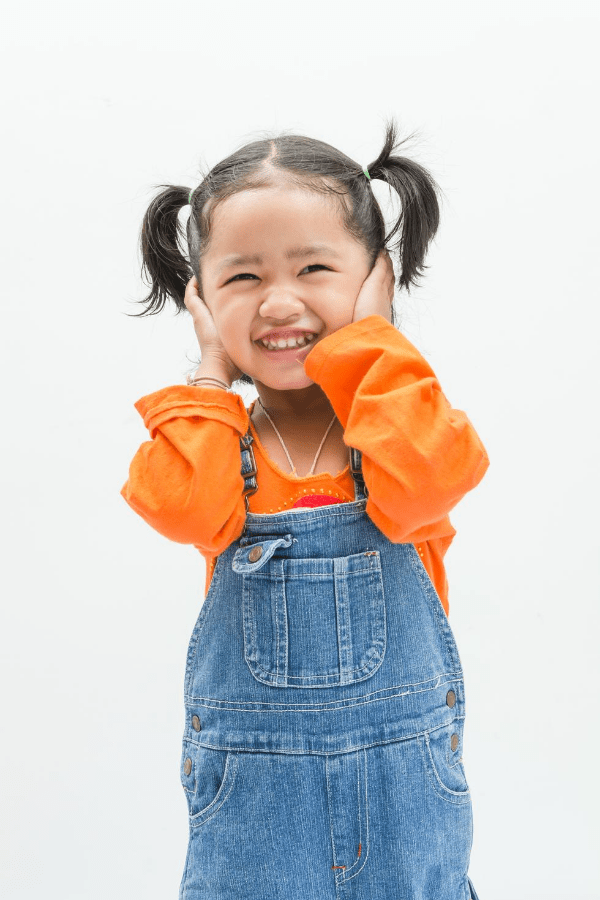 Little girl with a bible name puts her hands on her cheeks and smiles.