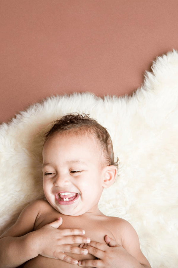 Baby boy lays on a white rug.