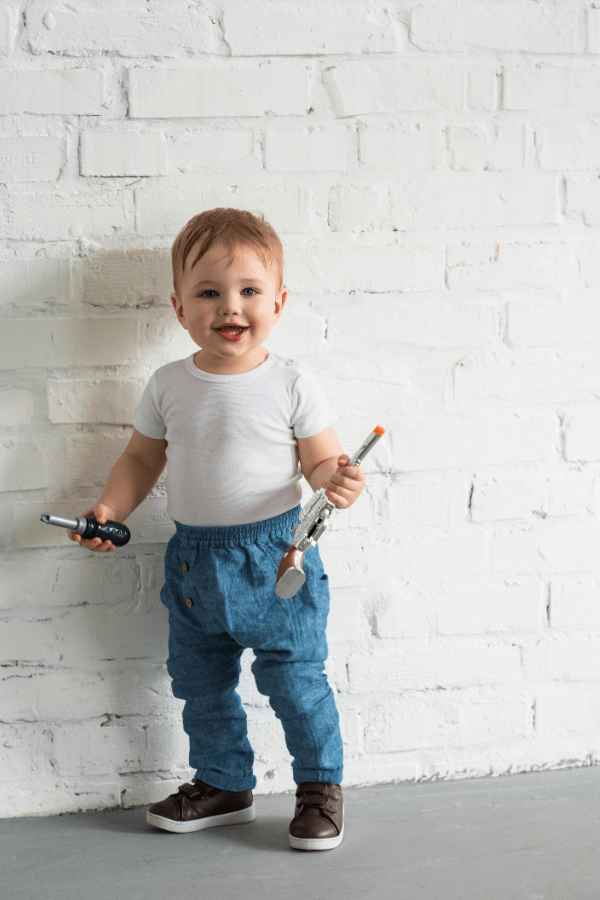 Baby boy holds tools.