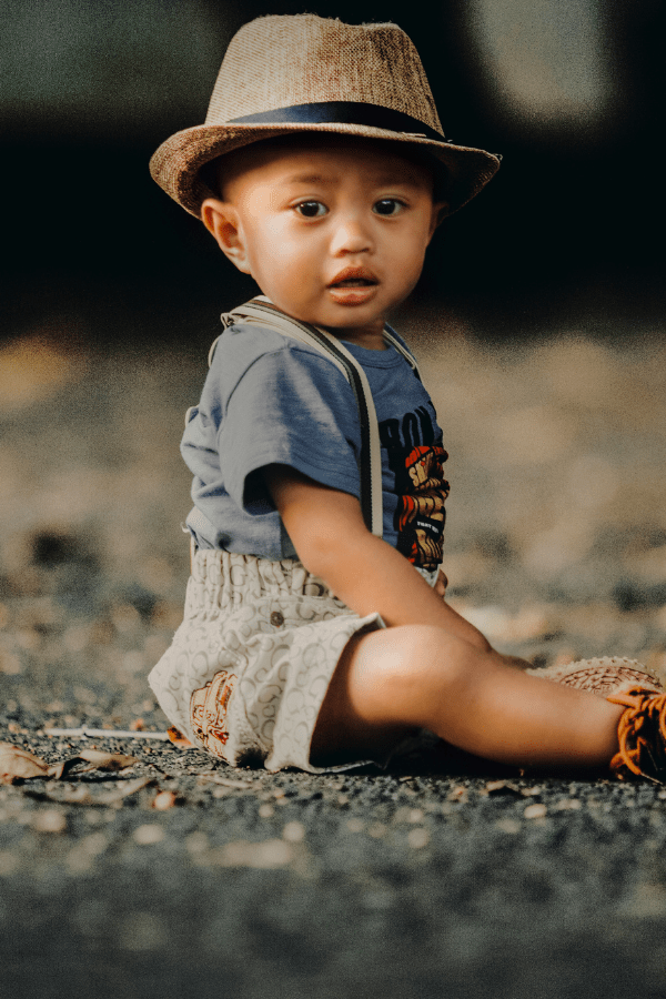 Baby boy sits on the ground wearing a hat and suspenders.