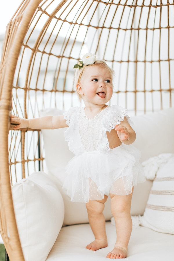 Baby girl stands on a chair for her first birthday.