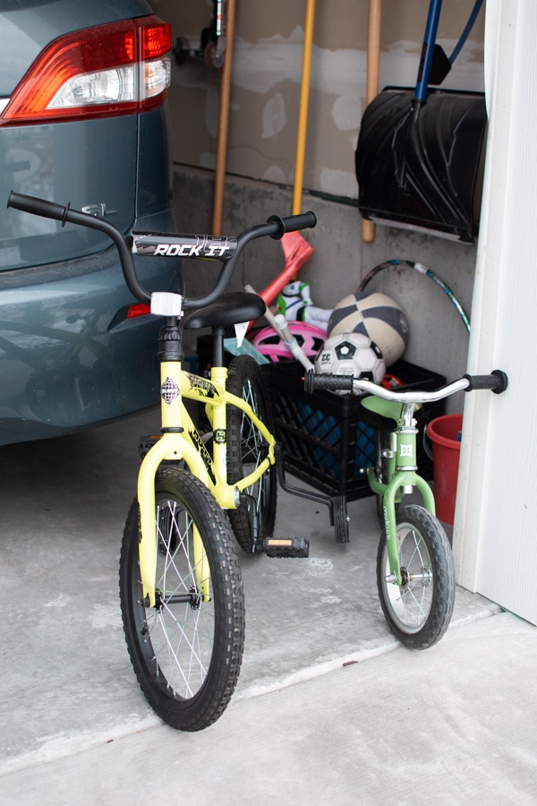 Two bikes in front of a garage.