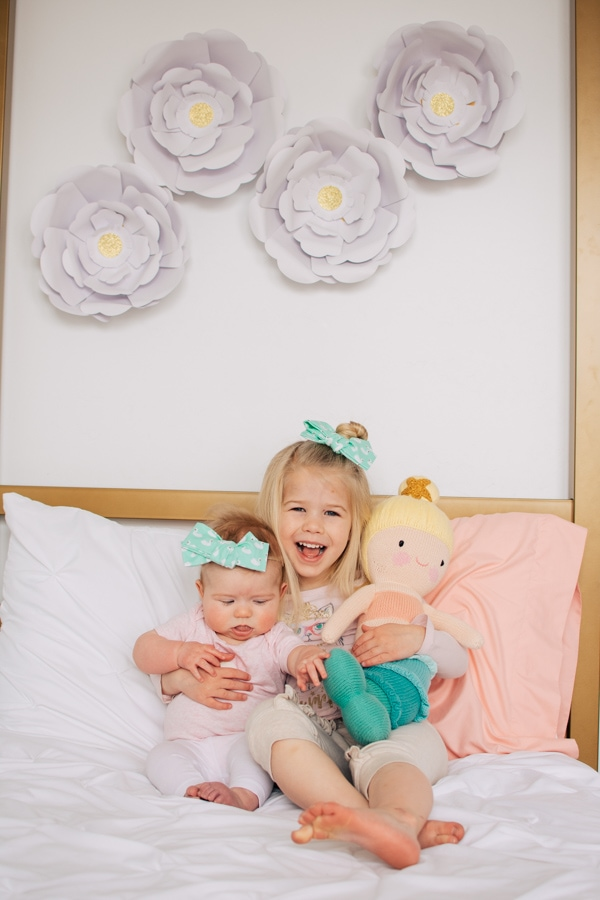 Two sisters holding a creative play toy on a bed.