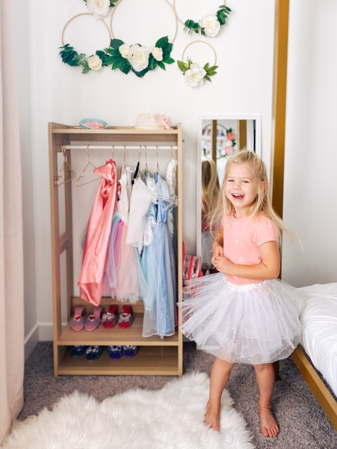 Girl twirls in front of her dress ups.