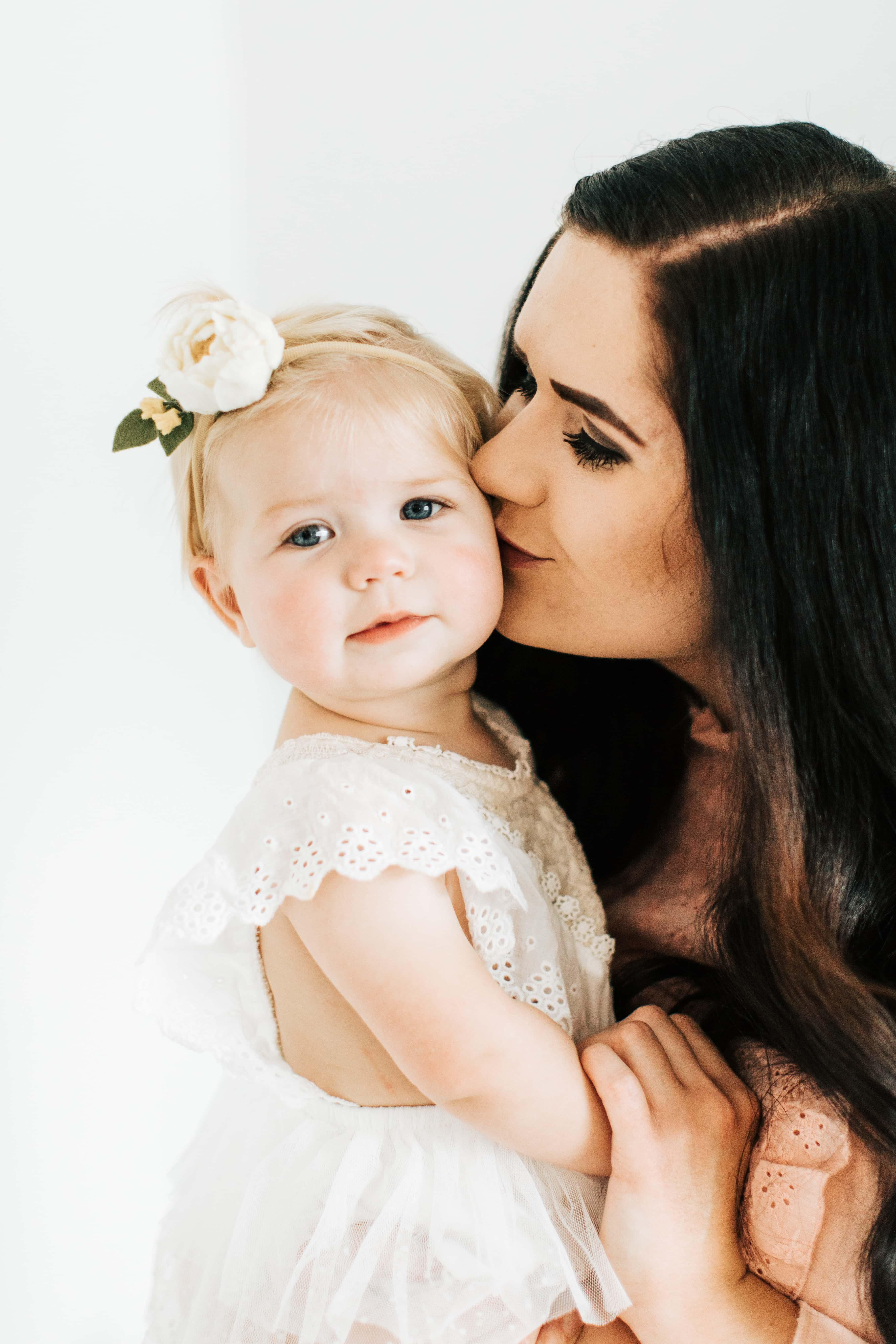 Mom kisses first birthday girl.