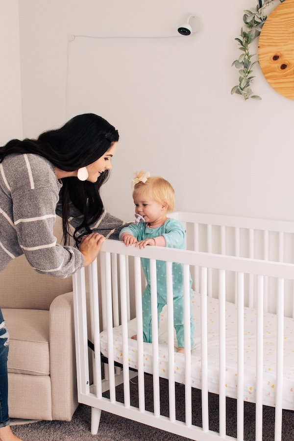 Mom puts baby in a crib with a Lumi monitor on the wall.