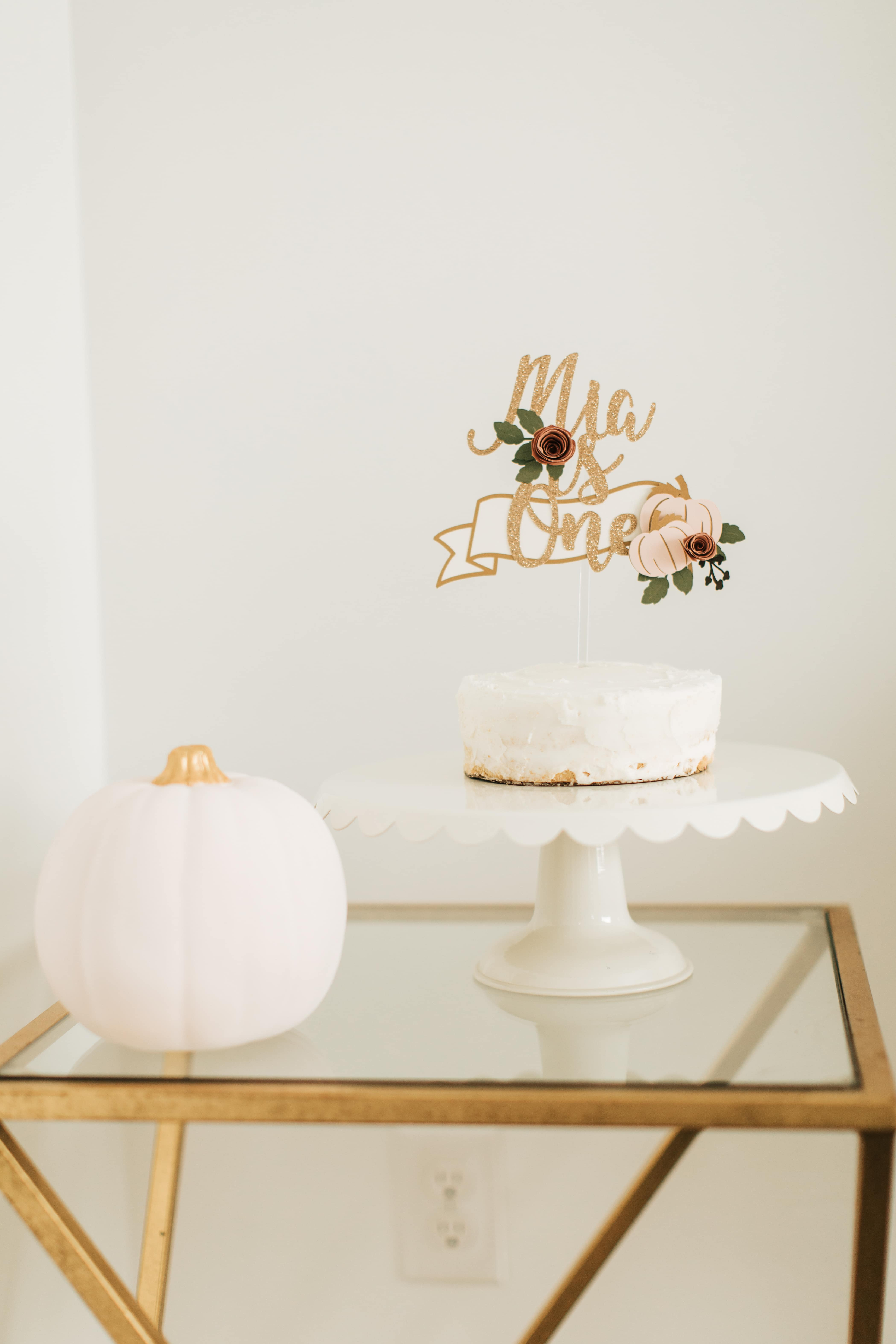 Pink and gold pumpkin birthday cake on a stand.