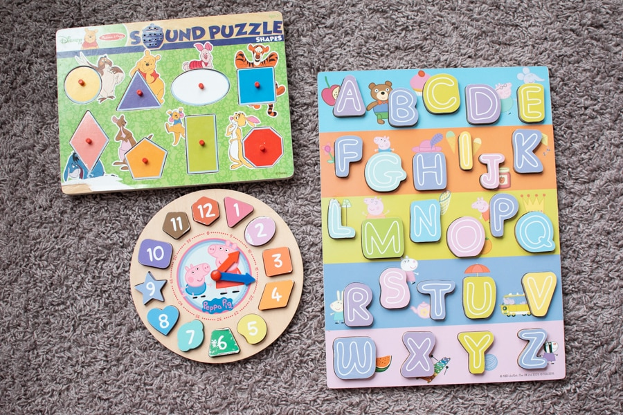 Three toddler puzzles on the floor.