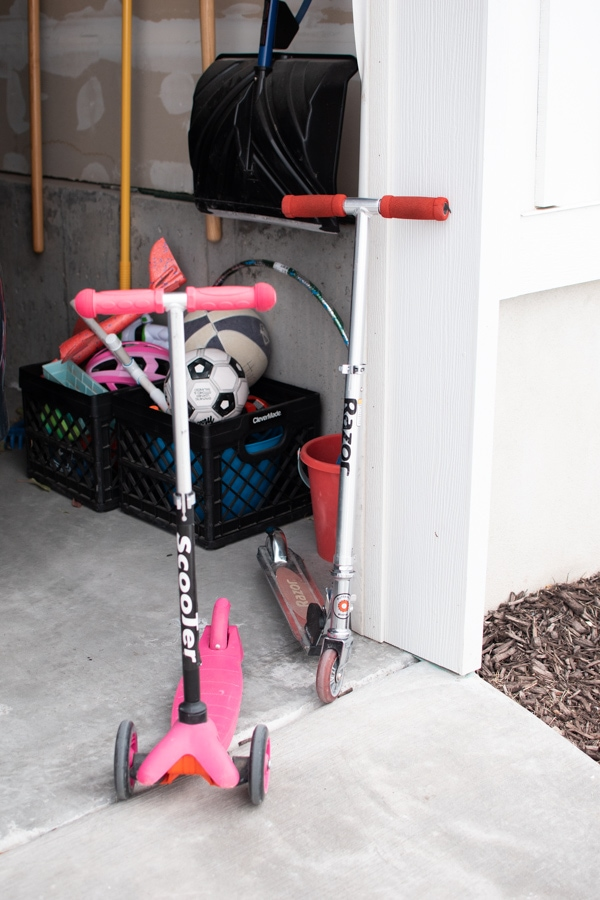 Two scooters standing in a garage.