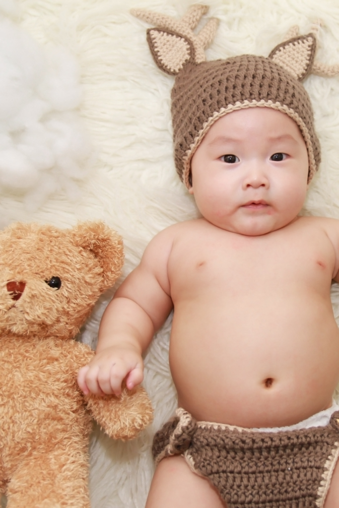 Baby boy wears a fox hat and diaper cover.