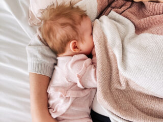 Mom breastfeeds baby girl on a bed.
