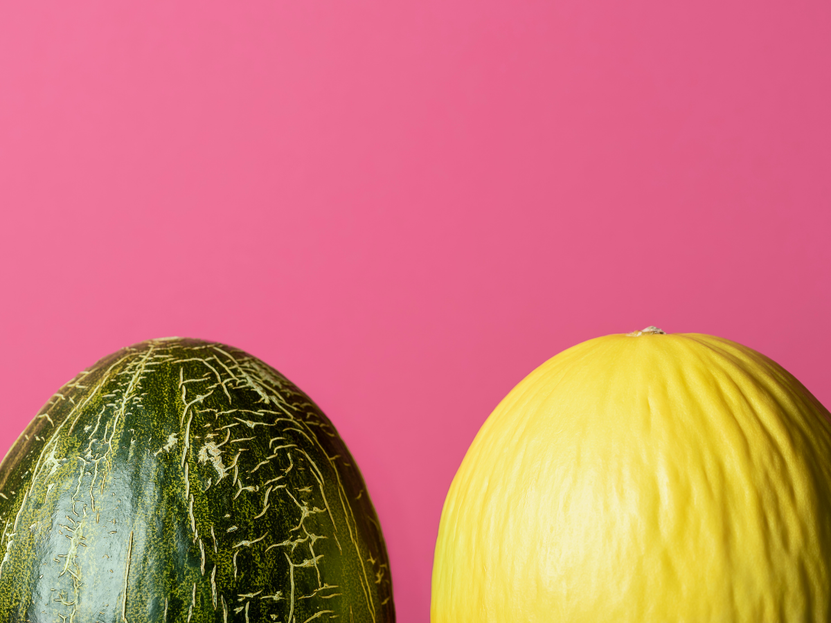Two melons in front of a pink background.