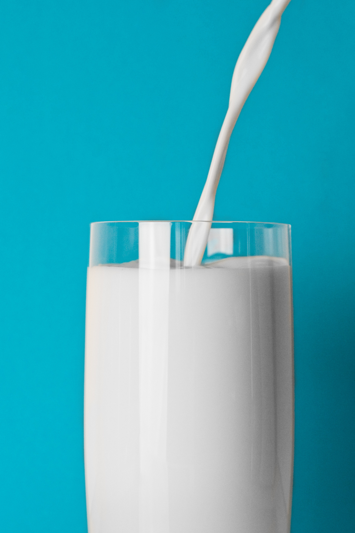 Glass of milk in front of a blue background.
