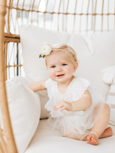 Baby girl wearing a white outfit sits on a chair.