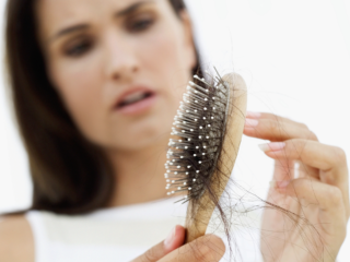 Woman holds brush filled with lost hair.