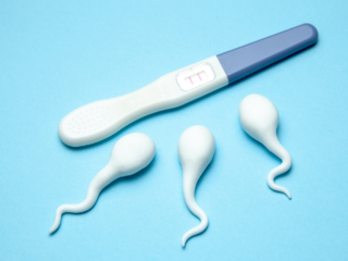 Positive pregnancy test on blue background.