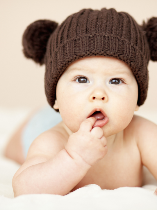 Baby wears brown crochet hat and smiles for camera.
