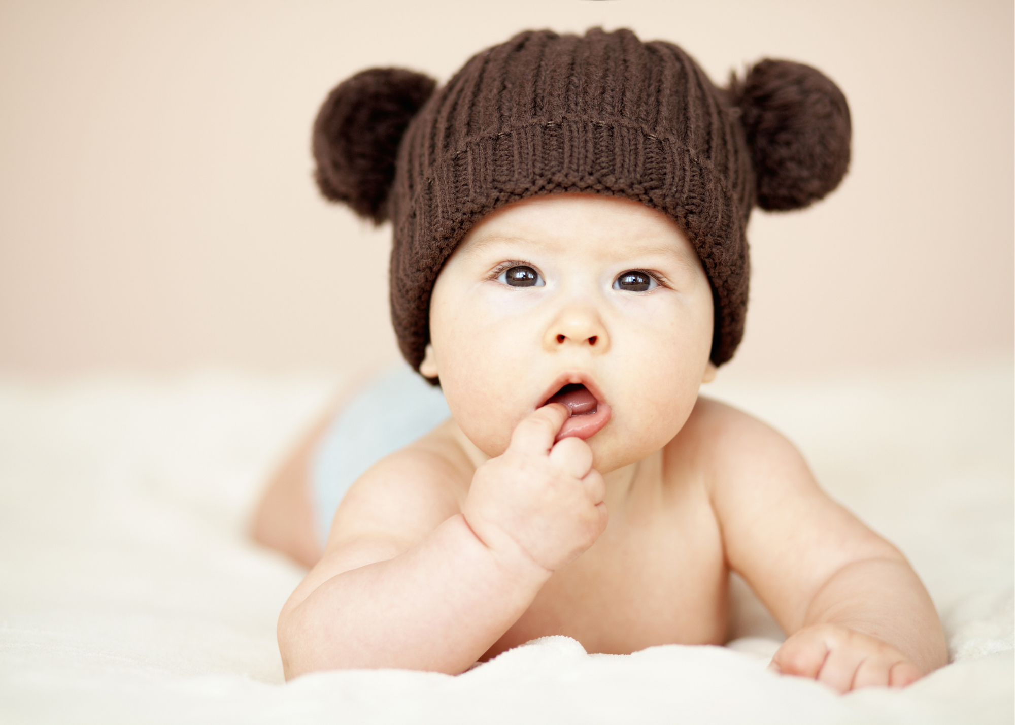 Baby wearing a brown crochet hat lays on a cream blanket and has finger in open mouth.