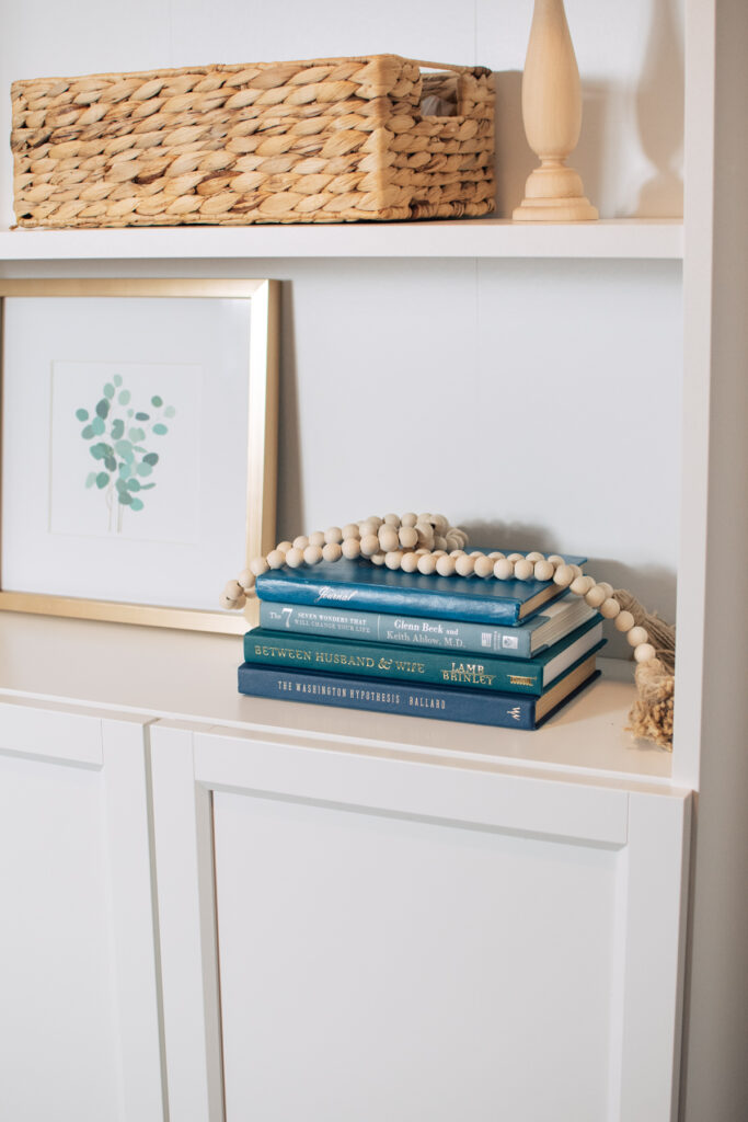 Bookshelf decor ideas with books and bead garland.