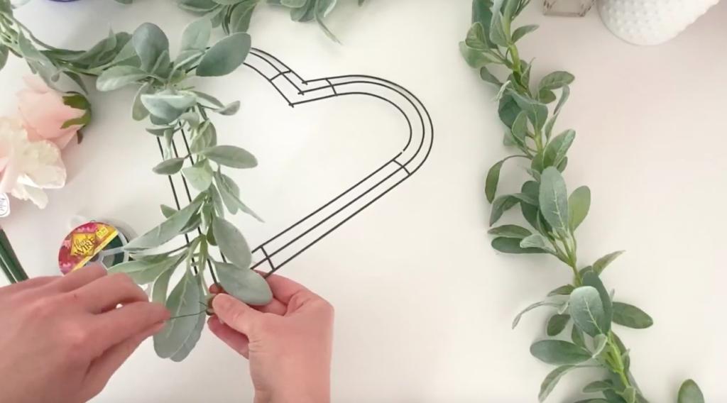 Woman puts a garland on a heart wreath frame.