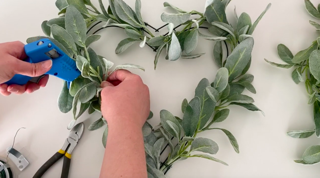 Woman hot glues pieces of garland on a heart wreath.