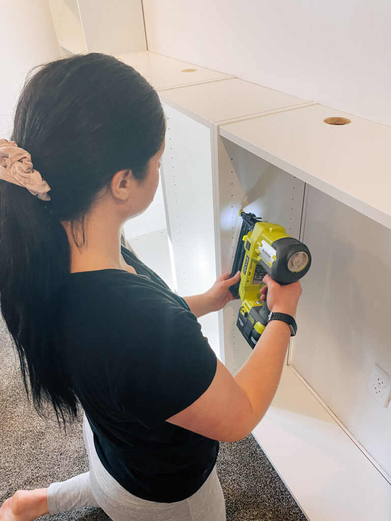 Woman uses a nail gun to secure bookcases.