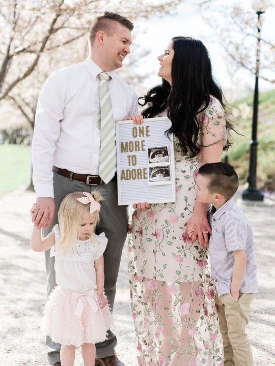 Family holds letter board baby announcement.