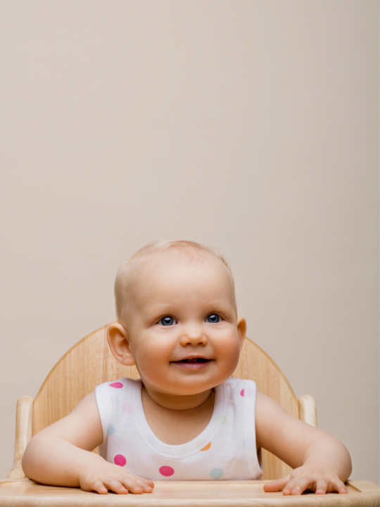 Baby girl smiles while sitting in a high chair.