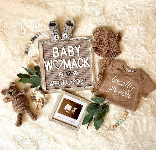 Flat lay with letter board and brown baby clothes.