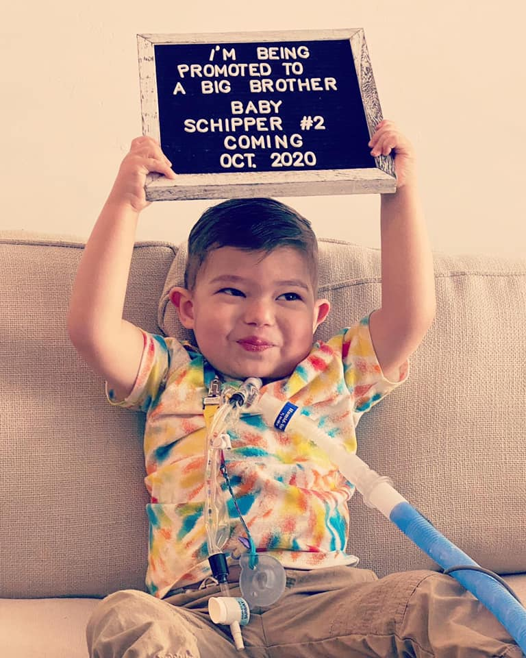 Little boy holds baby announcement board.
