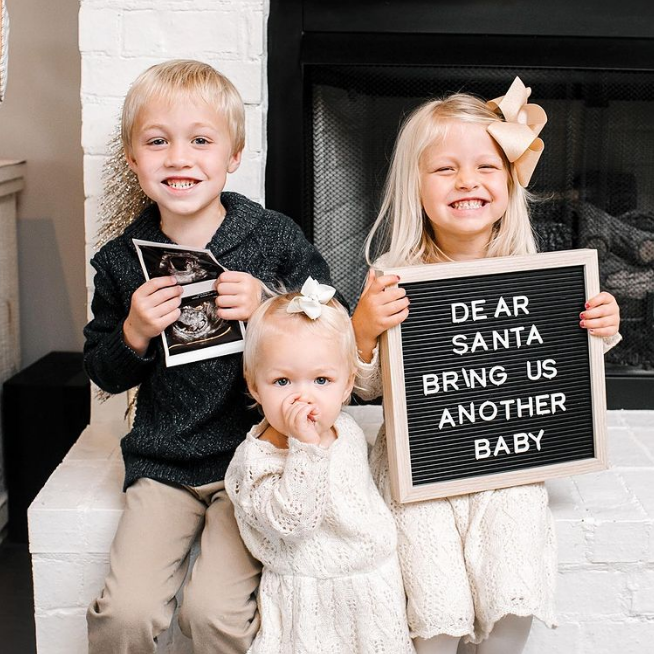 Siblings hold letter board and ultrasound photo.
