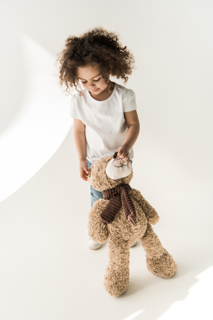 Toddler girl holds a teddy bear.