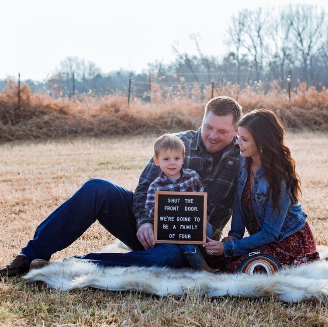 Family sits on blanket and holds black letter board.
