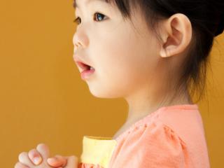 Toddler girl holds her hands together.