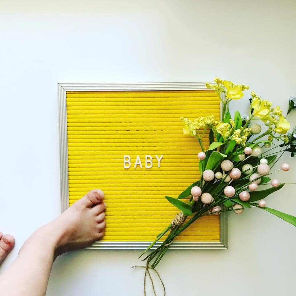 Yellow letter board baby announcement.